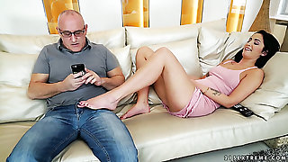 Mature white man on the couch with young and shunned brunette